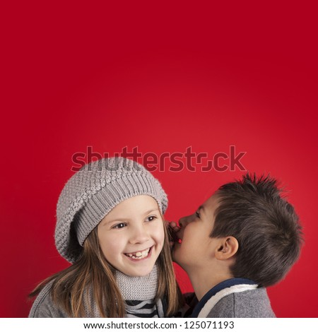 Couple of kids whispering on red background with copy space. Valentines day concept. - stock photo