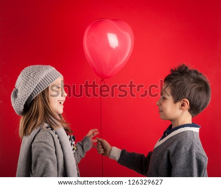 Couple of kids with red heart balloons on red background. Valentines day concept. - stock photo