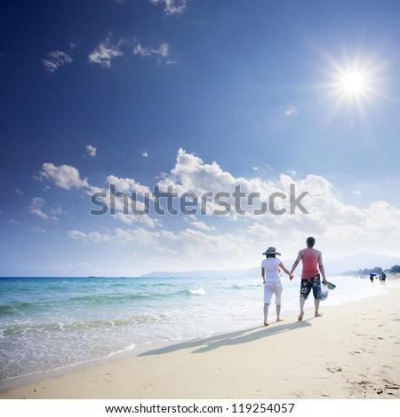 couple of live walking on beach - stock photo