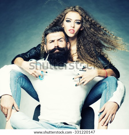 Couple of long-haired young beautiful woman holding two pairs of scissors sitting behind handsome bearded grey-haired man with moustache both looking forward on grey background, square picture - stock photo