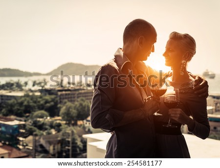 Couple of lovers at restaurant - Pretty woman and his man drinking wine at sunset on a romantic date - stock photo