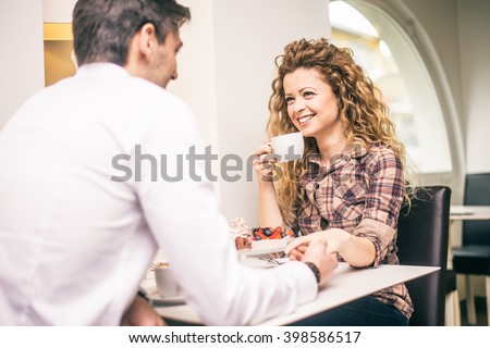 Couple of lovers drinking coffee and talking - Man holding hand of his girlfriend and flirting - Romantic date in a restaurant - stock photo