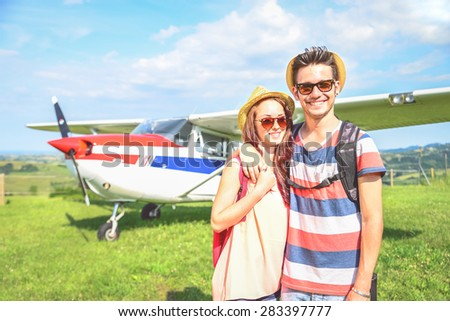 Couple of lovers taking a charter airplane - Tourists on vacation waiting their flight to go on excursion - People smiling and private plane on background - stock photo