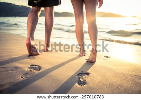 Couple of lovers walking on the each at sunset - Foot prints on the beach - stock photo
