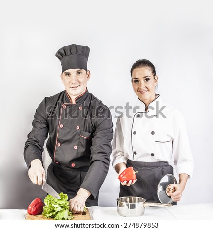 couple of man and woman standing near table with fresh vegetables and cooking healthy vegan food isolated on white background Isolated on gray background People wear new modern uniform  - stock photo