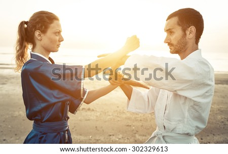 couple of martial artists training on the beach at sunrise  - stock photo