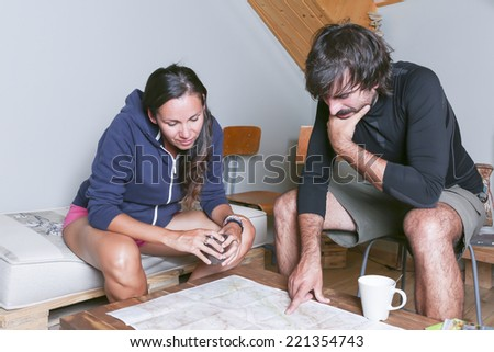 couple of mountaineers sitting pointing in a map the planning of the route in a shelter drinking a cup of coffee - focus on the mountaineers - stock photo
