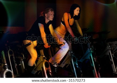couple of nice girls in a gym club with colored light effect - stock photo