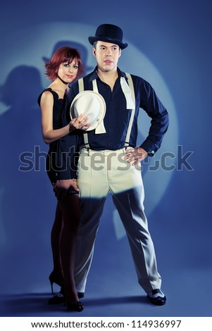 Couple of professional singers in retro style posing in costumes at studio. - stock photo