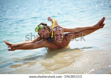 Couple of scubadivers looking at camera in water holding hands as if flying - stock photo