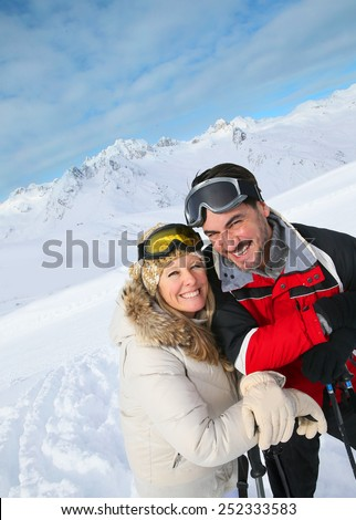 Couple of skiers enjoying winter vacation - stock photo