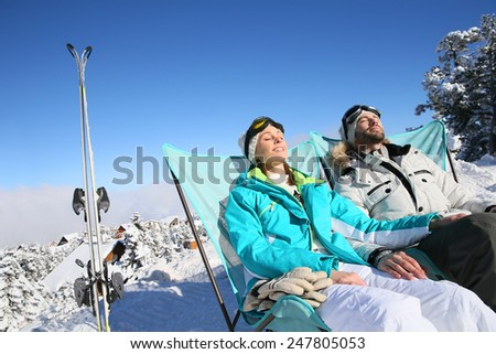 Couple of skiers sunbathing in long chairs - stock photo