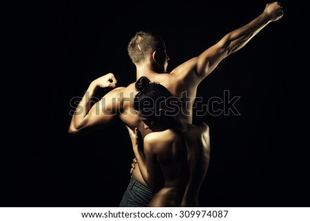 Couple of slim stripped girl embracing young boy with sexy strong muscular attractive body with raised arms and standing on studio black background, horizontal picture - stock photo