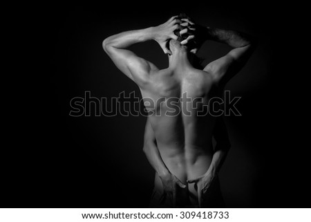 Couple of slim stripped woman embracing handsome young man with strong muscular body with raised hands standing in studio black and white copyspace, horizontal picture - stock photo