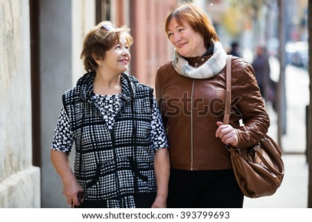 Couple of smiling mature women enjoying a city walk - stock photo
