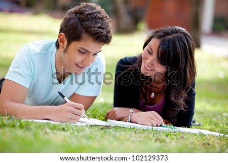 Couple of students lying outdoors and smiling - stock photo