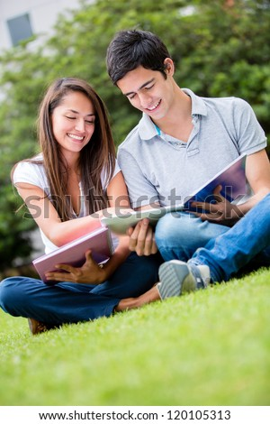 Couple of students outdoors looking very happy - stock photo