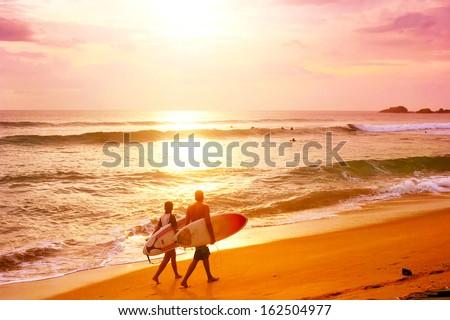 Couple of surfers walks along the beach in Hikkaduva - is the best surf paradise in Sri Lanka - stock photo