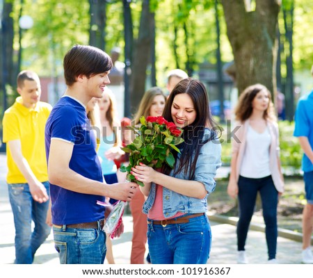 Couple of teenager on date outdoor. Group of people in background. - stock photo