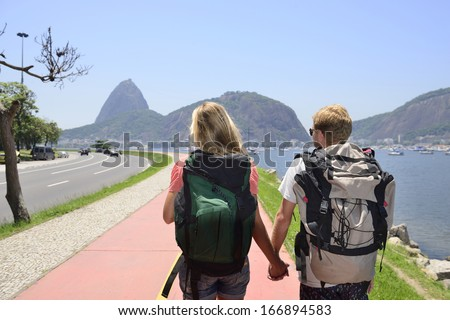 Couple of tourists backpackers walking through Rio de Janeiro with Sugar Loaf in the background. - stock photo