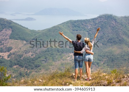Couple of tourists hiking in mountains, enjoying beautiful view of lagoon and small islands far away - stock photo