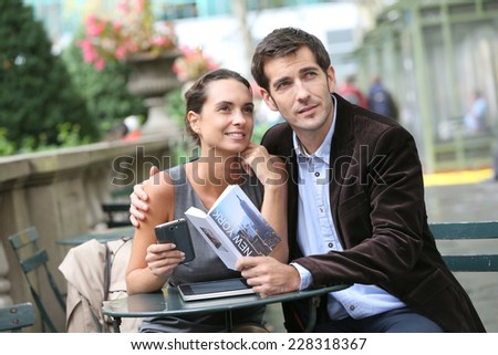 Couple of tourists in Bryant Park using smartphone and city guide - stock photo