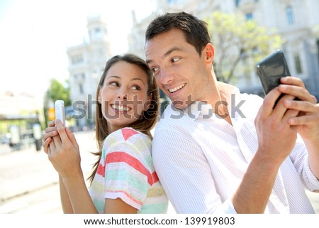 Couple of tourists in Madrid using smartphone - stock photo