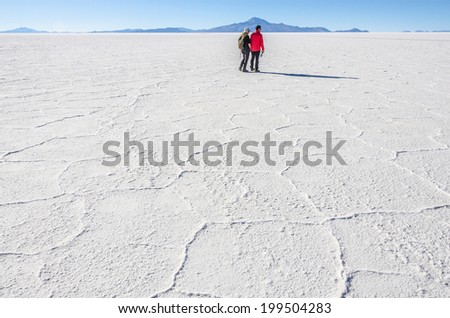 Couple of tourists in Salar de Uyuni, Bolivia - stock photo