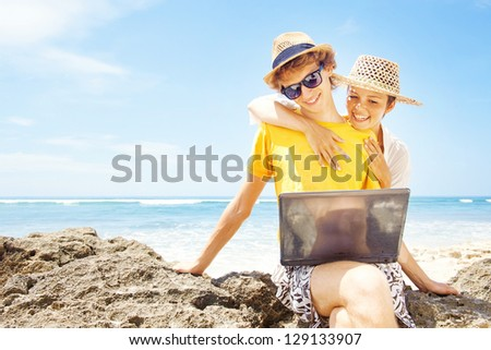 Couple of tourists on beach with laptop - stock photo