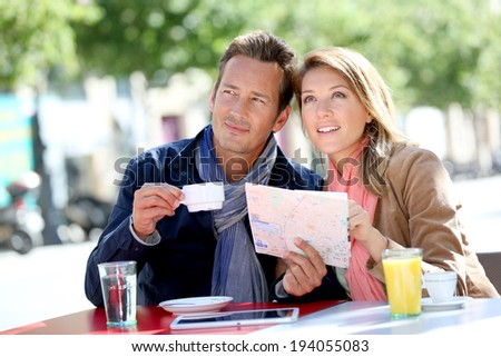 Couple of tourists reading city map - stock photo