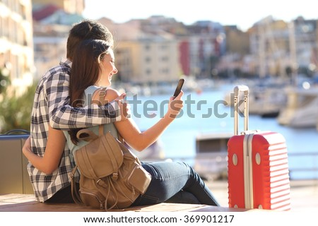 Couple of tourists sitting searching information or booking an hotel on a smart phone on vacations in a colorful port promenade - stock photo