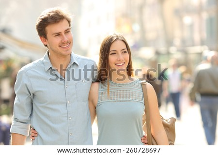 Couple of tourists taking a walk in a city street sidewalk in a sunny day - stock photo