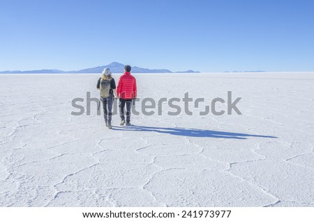 Couple of tourists walking at Salar de Uyuni, Bolivia - stock photo