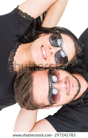 Couple of travelers resting layed down wearing shades or sunglasses - stock photo