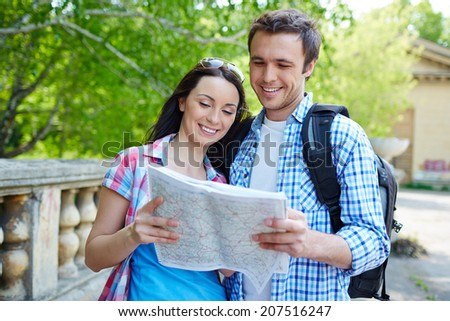 Couple of travelers studying map on journey - stock photo