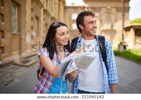 Couple of travelers with map deciding where to go sightseeing - stock photo