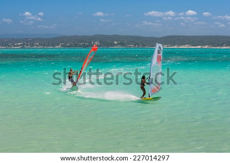 Couple of windsurfers in the vastness of the lagoon - stock photo