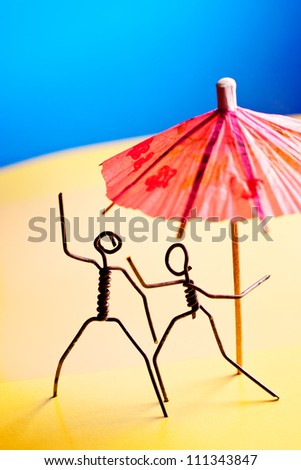 Couple of wire characters relaxing on a beach - stock photo
