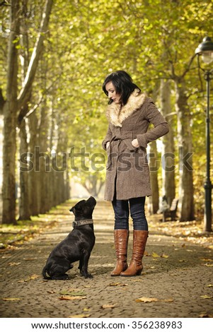 Couple of woman and her dog spending time in park - stock photo