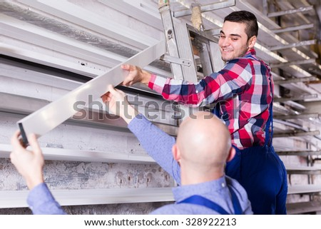 Couple of workmen inspecting window frames at factory indoor - stock photo