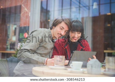 Couple of young beautiful caucasian man and woman business colleague seated on a bar using tablet and smartphone - technology, business, communication concept - stock photo