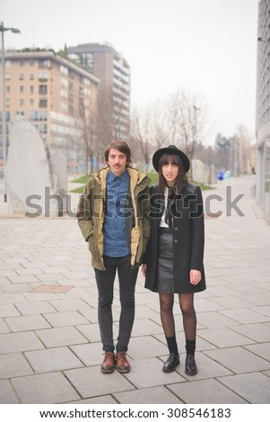Couple of young caucasian man and woman posing in the streets of the city hugging - carefreeness, friendship, love, youth concept  - stock photo