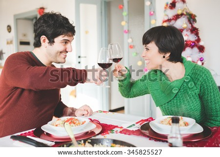 Couple of young handsome caucasian man and woman sitting on a table, having christmas meal, toasting with glasses of red wine, looking in the eyes, smiling - christmas, food, celebration concept - stock photo