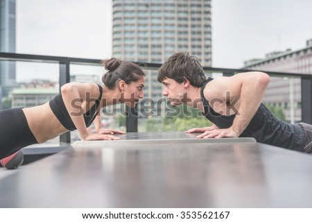 Couple of young handsome caucasian sportive man and woman doing push ups, facing each other, staring at each other's eyes - sportive, fitness, healthy, training concept - stock photo