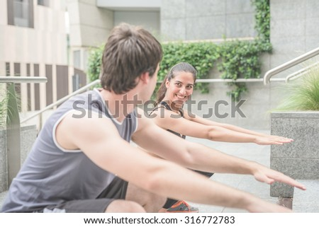 Couple of young handsome caucasian sportive man and woman doing squat in the city - focus on the woman looking and smiling at her friend - healthy, fitness, sportive concept - stock photo
