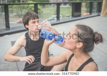 Couple of young handsome caucasian sportive man and woman drinking water from a bottle, having a break from training, he is overlooking left - relaxing, break, training concept - stock photo