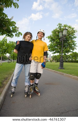 Couple of young man and woman rollerblading at park - stock photo