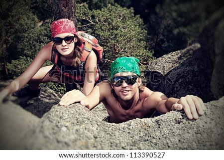 Couple of young people alpinists are climbing on a mountain. - stock photo