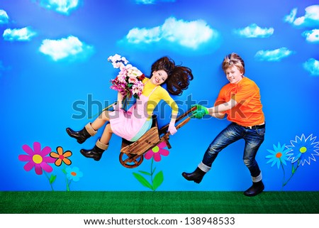 Couple of young people in love running with flowers in their hands. - stock photo