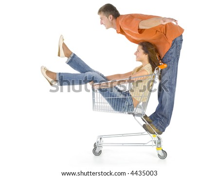 Couple of young people riding by trolley. Having fun. Isolated on white in studio. Boy trying to fly. Side view - stock photo